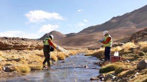 Dos peritos tomando muestras en un rio.